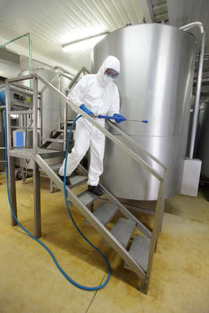 worker in white protective uniform with high pressure washer on stairs at large industrial process tank preparing to cleaning