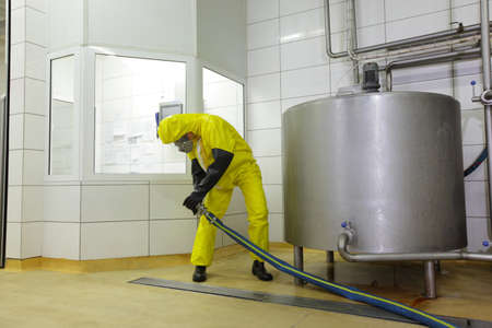 processing: technician in protective coveralls,with large hose at industrial tank in plant Stock Photo