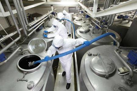 riesgo quimico: tres trabajadores en overoles trabajadores de protección que trabajan en grandes depósitos de plata en la planta Foto de archivo