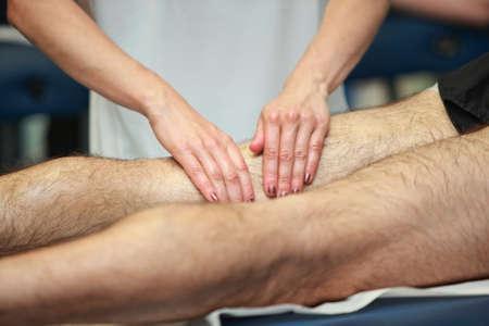 masaje deportivo: manos masajeando el muslo de atleta después de correr