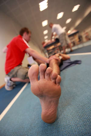 physiotherapist helping exhausted  athletes foot after running