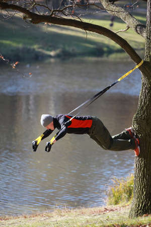 outdoor training: suspension workout at the river - man at the outdoor training at the river