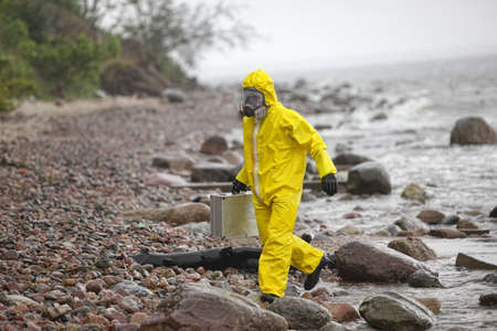 protective suit: Scientist in protective suit with silver case walking in on rocky beach - side view