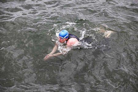 wetsuit: dynamic and fit swimmer in cap and wetsuit breathing swimming in dark sea water
