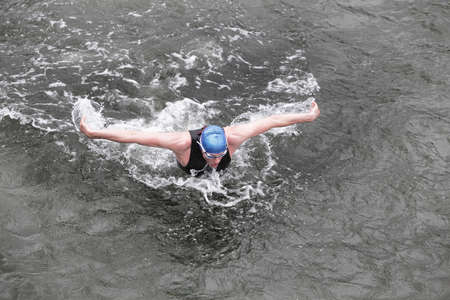 front raise: dynamic and fit swimmer triathlete in cap and wetsuit breathing performing butterfly stroke in dark sea water Stock Photo
