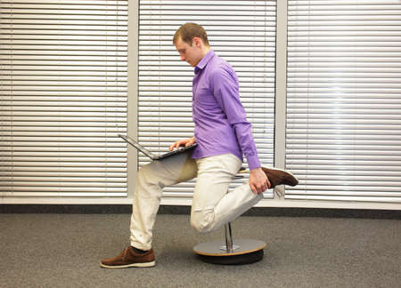 calf pain: leg exercise during office work -  man sitting on pneumatic stool, working with laptop in his office