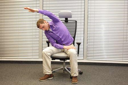 buena postura: Hombre que ejercita en la silla de oficina, estilo de vida saludable - vista frontal