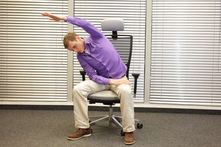 back exercise: man exercising on chair in office, healthy lifestyle - front view
