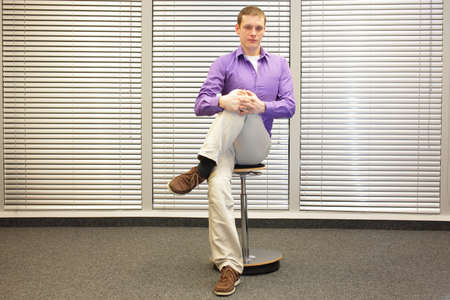 pneumatic: stretching legs in office -  man sitting on pneumatic stool exercising Stock Photo