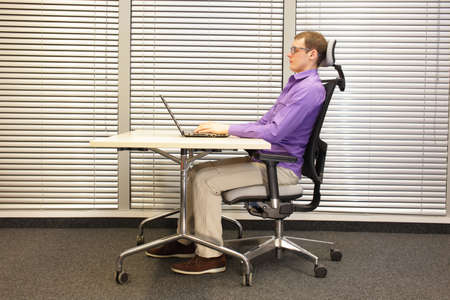 proper: correct sitting position at workstation. man in eyeglasses sitting on chair working with laptop