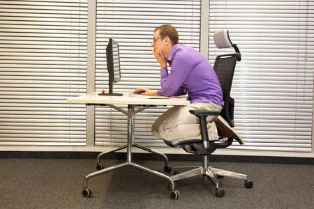 man kneeling: text neck - man in slouching position kneeling on ergonomic chair working with computer at desk Stock Photo
