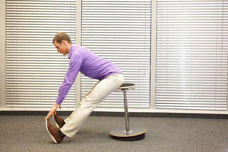 touching toes: man sitting on pneumatic stool exercising touching his toes in office