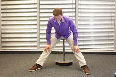lean: man stretching legs and back sitting on pneumatic stool in his office