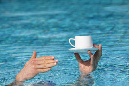 recommendation: recommendation -  best service - hand above water holding cup of coffee