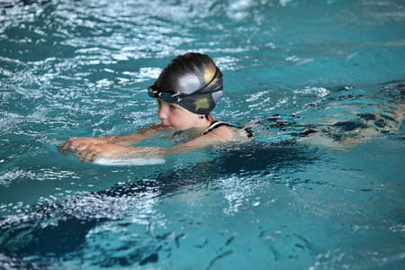swimming costumes: Close up of child practicing flutter kick with kick board in  indoor swimming pool