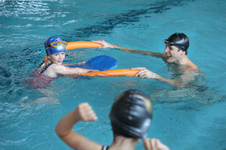 swimming costumes: father playing with daughters in swimming pool - healthy lifestyle Stock Photo