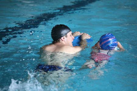 Close up of swimming lesson - child  practicing flutter kick with kick board  with instructor in  indoor swimming pool -back view Standard-Bild