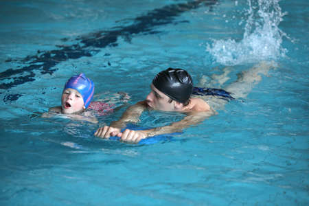 swimming costumes: Close up of swimming lesson - child  practicing flutter kick with kick board  with instructor in  indoor swimming pool - front view Stock Photo