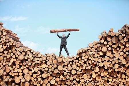 Hardworking Business Man op de top van grote stapel stammen het tillen van zware log - vooraanzicht