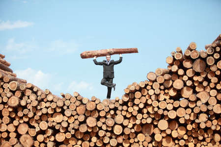 heavy lifting: business man on top of large pile of cut wooden logs ,standing on one hand, lifting heavy log, front view