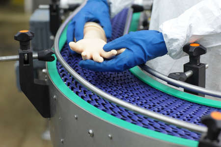 bionic: scientist at conveyor belt controlling  artificial bionic hand . a concept of spare body parts mass production Stock Photo
