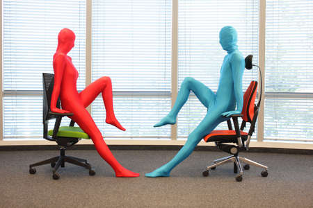 skintight: anonymous couple in full body  elastic suits exercising with chairs in office Stock Photo
