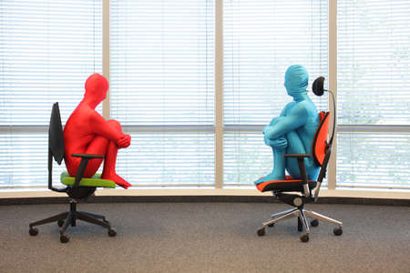 regulating: anonymous couple in full body  elastic suits sitting on armchairs in sunny space
