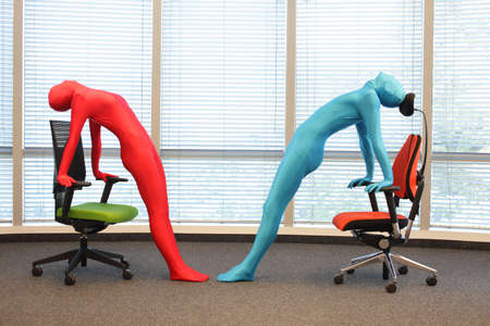 anonymous couple in full body  elastic suits exercising with chairs in office Stock Photo