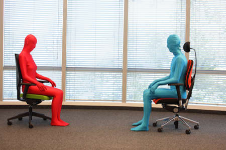 skintight: anonymous couple in full body  elastic suits sitting on armchairs in sunny space