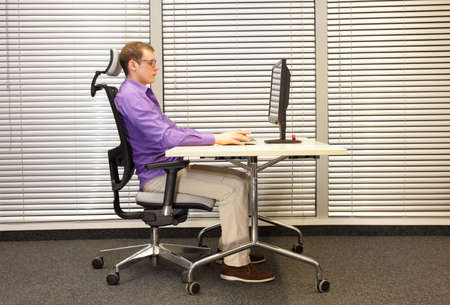 position: correct sitting position at computer. man on chair working at desk in office
