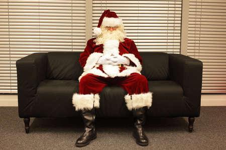 needless: waiting for christmas job, santa claus sleeping on sofa in office Stock Photo