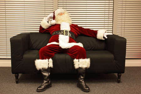 needless: ready santa claus waiting for christmas job sitting on sofa in office Stock Photo
