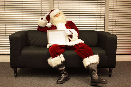 needless: Santa Claus sitting on sofa in his office holding blank whiteboard with space for copy - lack of motivation Stock Photo