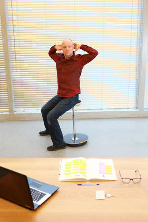office desk: middle age man stretching arms, relaxing neck - short break for exercise on pneumatic stool in office