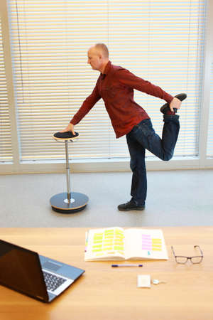 leg exercise during office work - middle age  standing man stretching  on pneumatic stool in his office Stock Photo