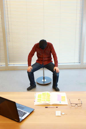 dangerous ideas: anonymous male in black sack on head resting on pneumatic chair in the office - burnout syndrome