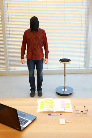 stool: anonymous man in black sack on head standing in office