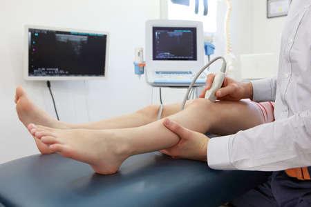 de rodillas: Ecografía de articulación de la rodilla del niño - Diagnóstico Foto de archivo