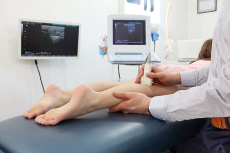 lower limb: Ultrasound of girls knee-joint - diagnosis Stock Photo