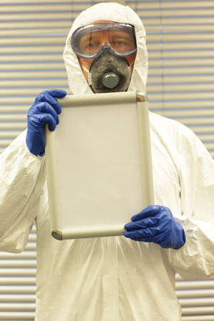 neutralizer: scientist in coveralls,  goggles,mask and blue gloves holding blank whiteboard with space for copy