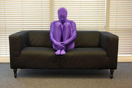 soledad: la soledad - el anonimato, torcida, deprimido, hombre sentado en el sofá en la oficina, Foto de archivo