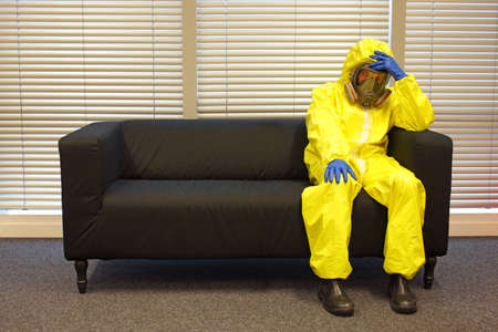 air pollution - professional in protective clothing, mask and gloves,sitting and relaxing on the couch in office