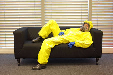 professional in protective clothing, mask and gloves, lying and relaxing on the couch in office Stock Photo