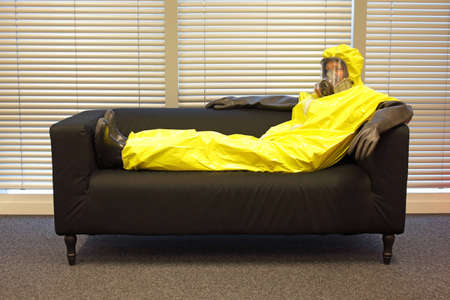 professional in protective clothing, mask and gloves, sitting and relaxing on the couch in office Stock Photo