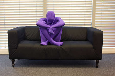 needless: loneliness - anonymous, crooked,depressed,man sitting on sofa in office,