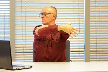uptight: middle age balding man relaxing neck - stretching arm - short break for exercise on chair in office