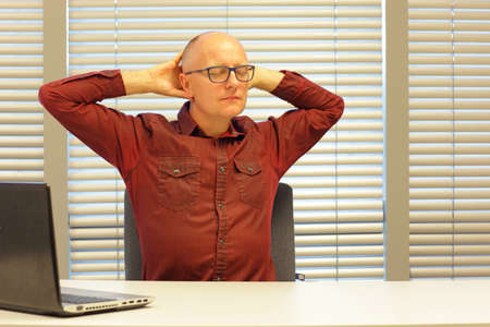 uptight: middle age balding man relaxing neck - stretching arms - short break for exercise on chair in office Stock Photo