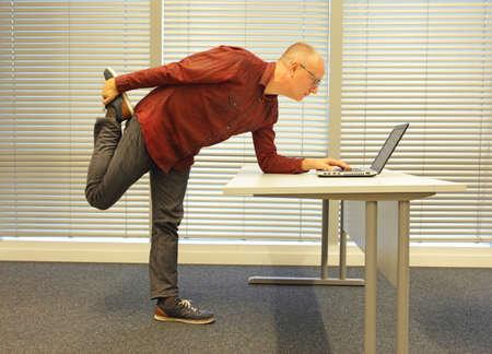 事務作業の彼のオフィスでラップトップを読んで眼鏡男の中年ハゲ男が立っている時に脚の運動 写真素材