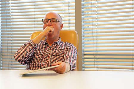tired,yawning middle age man in eyeglasses,with tablet