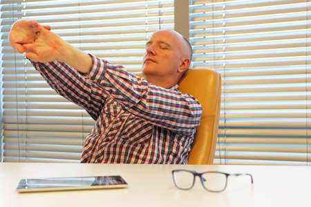 uptight: middle age balding man  stretching arms - short break for exercise on chair in office